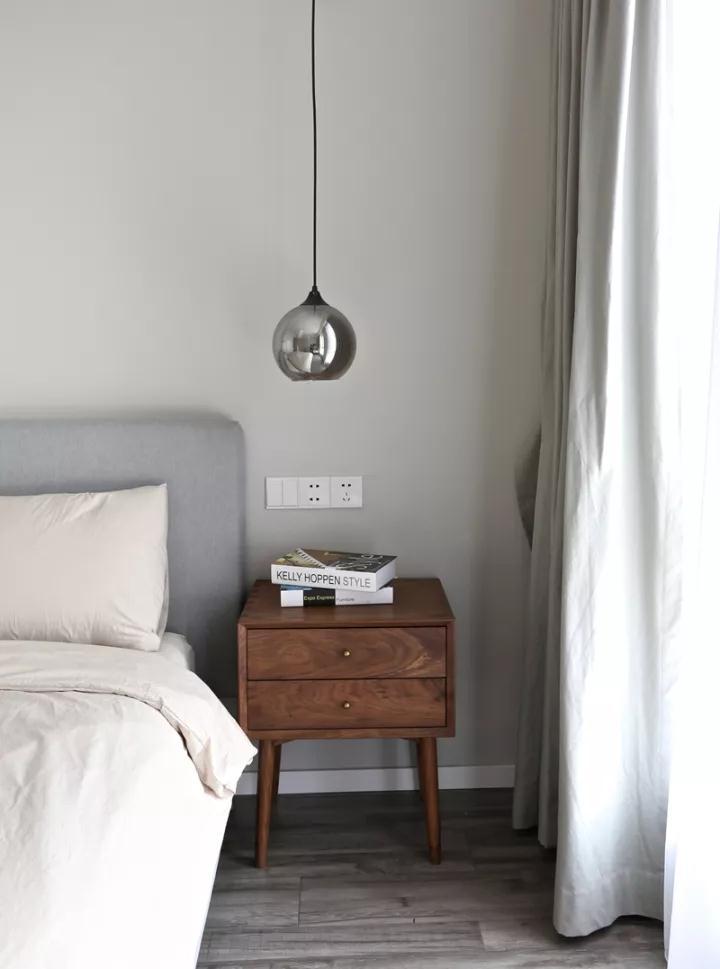 主卧床头柜选自杭州的家具品牌一屿,上方是镜面小吊灯.图片
